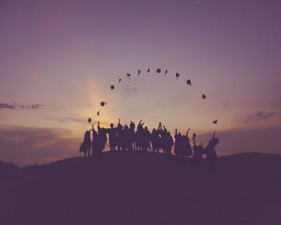 Skupina diplomiranih studenata na brijegu u suton baca kape u zrak.