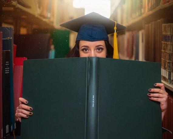 Diplomantica s knjigom u knjižnici.
